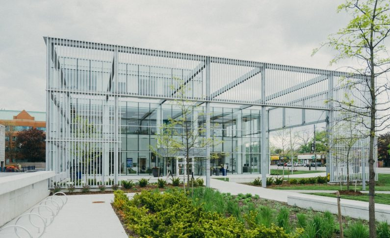 A Metal Structure With a Glass Building Facade at the Back